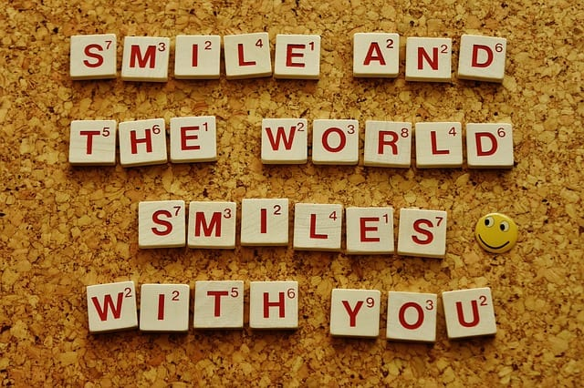 Smile and the world smiles with you written in Scrabble letters