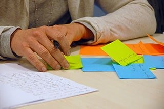 Image: person writing on sticky notes